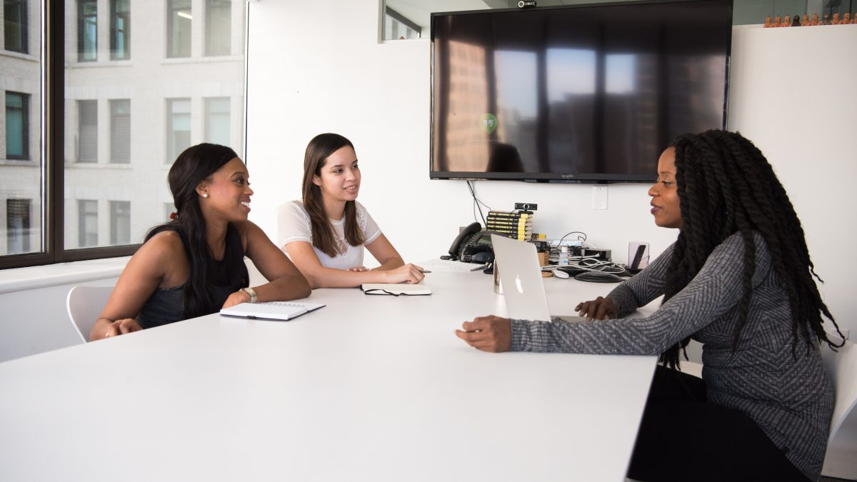 Three smiling women sitting at a white conference table having a meeting.